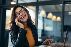 Усмехаясь бизнес-леди в вскользь говорить на телефоне стоковое фото