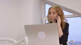 Усмехаясь бизнес-леди говоря работой промежутка времени мобильного телефона на ноутбуке в офисе сток-видео