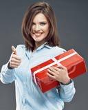 Усмехаясь бизнес-леди держит красный большой палец руки выставки подарочной коробки вверх стоковое изображение rf