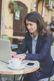 Усмехаясь бизнес-леди работая на компьтер-книжке на кафе Стоковые Изображения