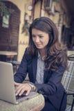 Усмехаясь бизнес-леди работая снаружи, на компьтер-книжке Стоковые Изображения