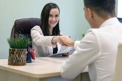 Усмехаясь бизнес-леди тряся руки с молодым бизнесменом на столе в офисе Концепция интервью, согласования, партнера Стоковые Изображения
