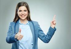 Усмехаясь бизнес-леди указывая на экземпляр размечает и выставки thumb вверх Стоковое Изображение RF