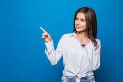 Усмехаясь бизнес-леди указывая палец на космос экземпляра голубая стена стоковое фото