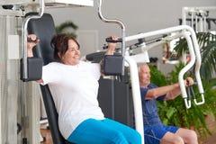 Усмехаясь более старая женщина разрабатывая на спортзале стоковые фото