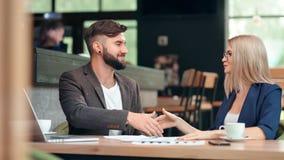 Усмехаясь бородатая коммерсантка бизнесмена довольно делая контракт подписания дела на неофициальном заседании сток-видео