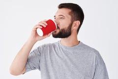 Усмехаясь бородатый кофе дегустации человека от бумажного стекла стоковые фото