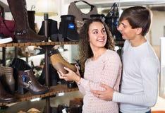 Усмехаясь ботинки зимы пар покупая в магазине Стоковые Изображения