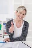 Усмехаясь более старая коммерсантка сидя на столе с большими пальцами руки вверх стоковые фото