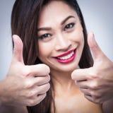 Усмехаясь большие пальцы руки девушки успешные поднимают о'кеы Стоковые Изображения