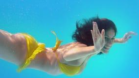 Усмехаясь брюнет в желтом бикини плавая под водой сток-видео