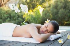 Усмехаясь брюнет лежа на poolside полотенца окруженном цветками Стоковые Фотографии RF