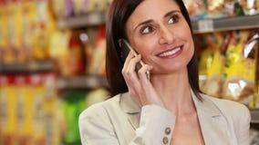 Усмехаясь брюнет зноня по телефону пока ходящ по магазинам акции видеоматериалы