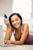 Усмехаясь брюнет используя компьтер-книжку и держать кредитную карточку Стоковая Фотография