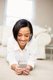 Усмехаясь брюнет используя smartphone Стоковое Изображение