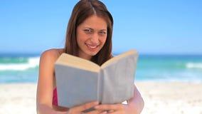 Усмехаясь брюнет наслаждаясь солнцем пока держащ книгу видеоматериал