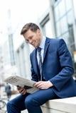 Усмехаясь бумага чтения бизнесмена на outdoors Стоковая Фотография