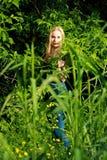 Усмехаясь блондинка в лесе Стоковая Фотография