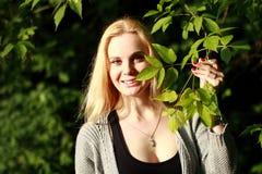 Усмехаясь блондинка в солнечном лесе Стоковое Изображение