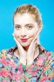 Усмехаясь блондинка с чувственными губами и улучшает кожу нося красочную рубашку на голубой предпосылке в студии женщина внимател Стоковая Фотография RF