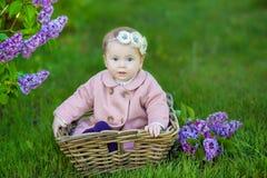 Усмехаясь венок цветка ребёнка 1-2 годовалый нося, держа букет сирени outdoors смотреть камеру время весны лета стоковое фото