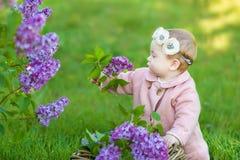 Усмехаясь венок цветка ребёнка 1-2 годовалый нося, держа букет сирени outdoors смотреть камеру время весны лета стоковое изображение rf
