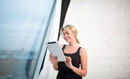 Усмехаясь видео девушки битника наблюдая в социальной сети через сенсорную панель, стоя в современном интерьере Стоковые Фото