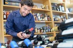 Усмехаясь вино бутылки клиента покупая на винном магазине Стоковые Фото