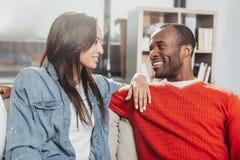 Усмехаясь влюбленныеся человек и женщина сидя совместно Стоковые Фото
