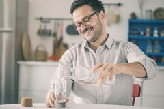Усмехаясь вода молодого человека лить от бутылки к стеклу стоковые изображения rf
