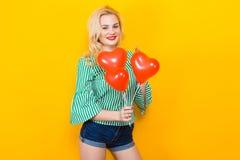 Усмехаясь воздушные шары белокурым владением женщины в форме сердц Стоковые Фотографии RF