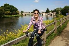 Усмехаясь восточная азиатская женщина с велосипедом на солнечный день стоковое фото