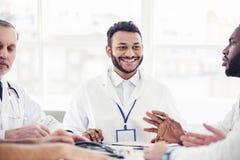 Усмехаясь врач слушая его коллеги на встрече Стоковые Фотографии RF