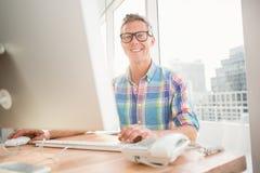 Усмехаясь вскользь бизнесмен работая с компьютером Стоковая Фотография