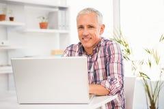 Усмехаясь вскользь бизнесмен работая с компьютером Стоковая Фотография RF