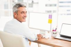 Усмехаясь вскользь бизнесмен работая с компьютером Стоковое Изображение
