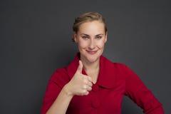 Усмехаясь выставка большого пальца руки бизнес-леди поднимающая вверх изолированная темная предпосылка Стоковое Изображение RF