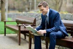 Усмехаясь газеты чтения бизнесмена в парке Стоковое Фото