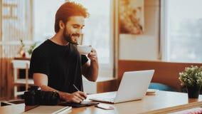 Усмехаясь Гай выпивает чай пока работающ на ноутбуке стоковая фотография