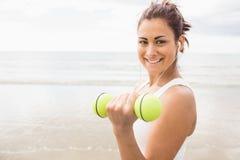 Усмехаясь гантели sporty женщины поднимаясь на пляже Стоковые Фотографии RF
