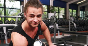 Усмехаясь гантель мышечного человека поднимаясь сток-видео