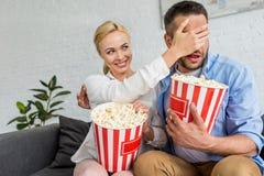 усмехаясь глаза женщины закрывая, который нужно экономно расходовать пока ел попкорн и смотреть ТВ стоковое фото rf