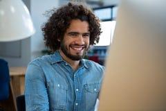 Усмехаясь график-дизайнер работая на компьютере Стоковая Фотография