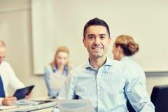 Усмехаясь группа в составе предприниматели встречая в офисе Стоковое Изображение RF