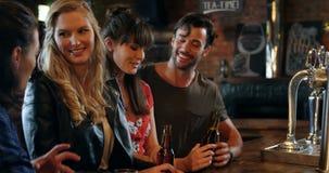 Усмехаясь группа в составе друзья взаимодействуя пока имеющ бутылку пива сток-видео