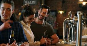 Усмехаясь группа в составе друзья взаимодействуя пока имеющ бутылку пива акции видеоматериалы