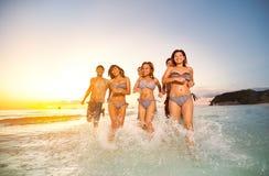 Усмехаясь группа в составе друзья играя совместно на пляже Стоковые Изображения RF