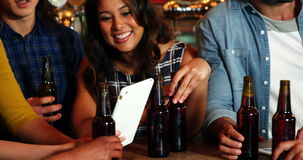 Усмехаясь группа в составе друзья используя цифровую таблетку пока имеющ бутылку пива видеоматериал