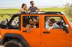 Усмехаясь группа в составе друзья путешествуя автомобилем совместно Стоковые Изображения RF