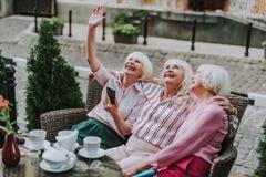 3 усмехаясь дамы сидя и смотря вверх стоковые изображения rf
